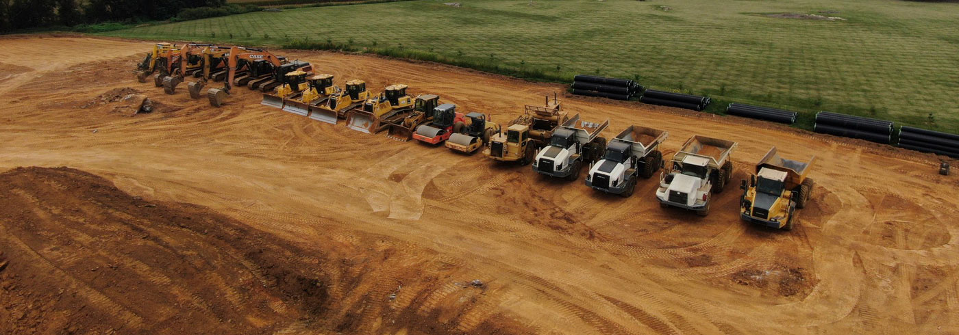 Various equipment lined up in a newly excavated field[::]H.L. Wiker has the equipment to handle any size job